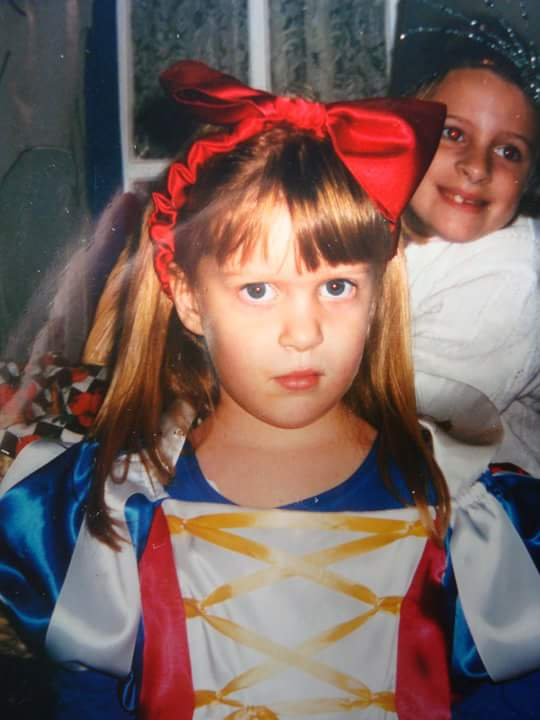 Image of Diana Muzina as a kid in a halloween costume giving a condescending look.